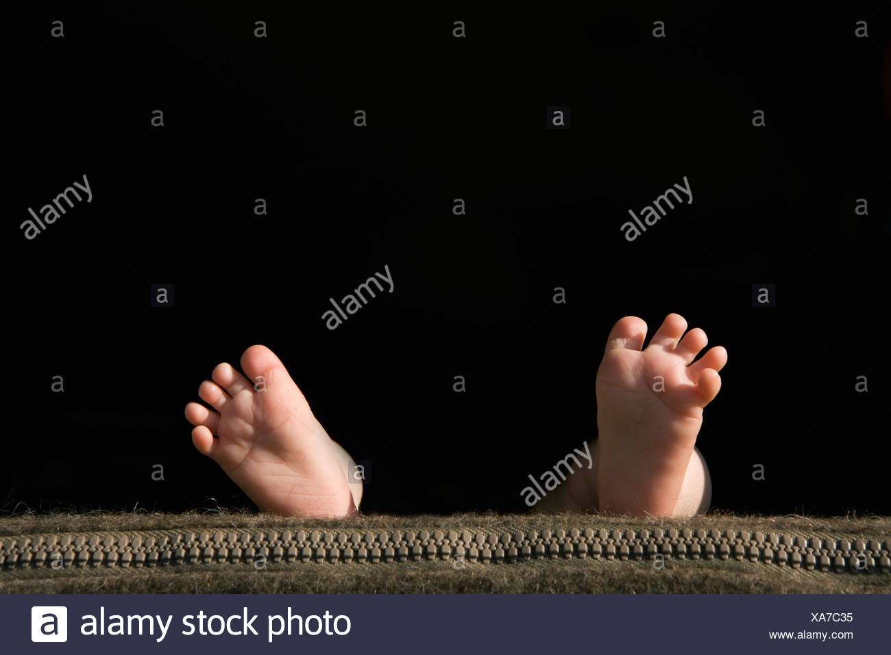 The soles of a baby's feet lying on a pillow - Stock Image