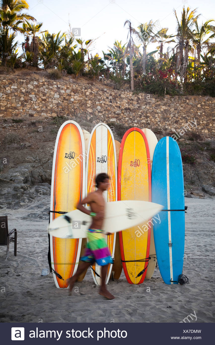 A surfer runs to the waves next to a stack of boards at Los Cerritos near Pescadero, Mexico. - Stock Image