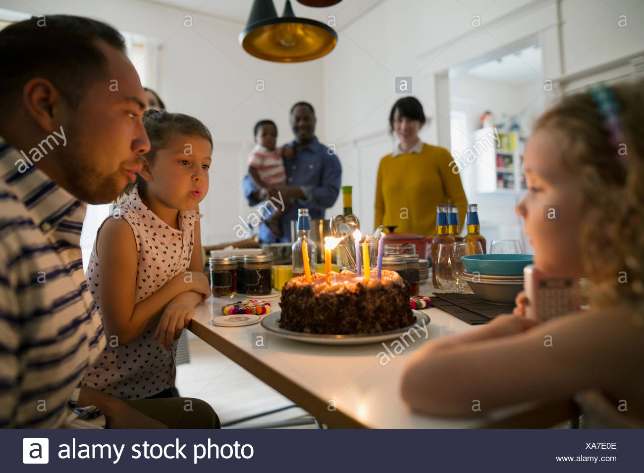 Father and daughters blowing out birthday cake candles at party - Stock Image