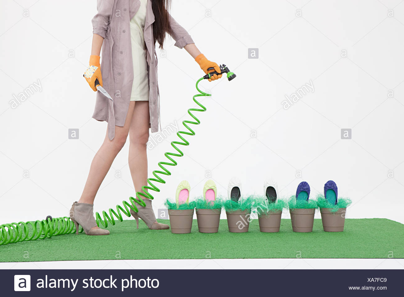 Woman with hosepipe and shoes in flower pots - Stock Image