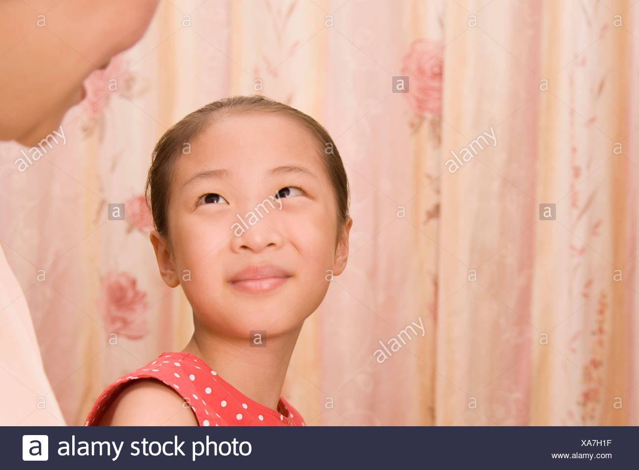 Close-up of a girl looking at her grandmother and smiling - Stock Image