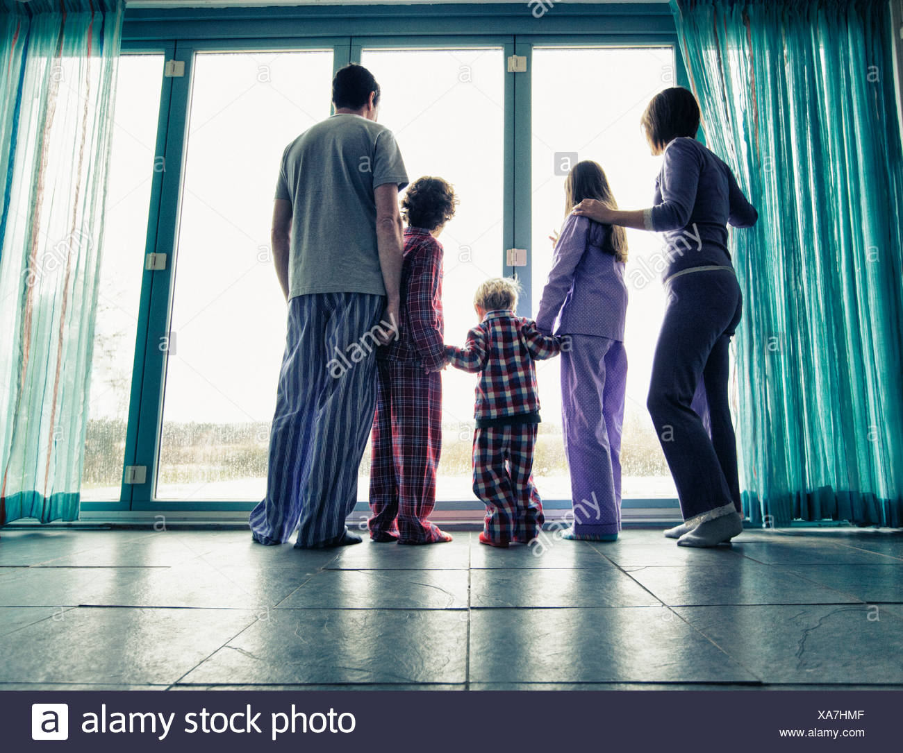 Family in pajamas looking out window Stock Photo
