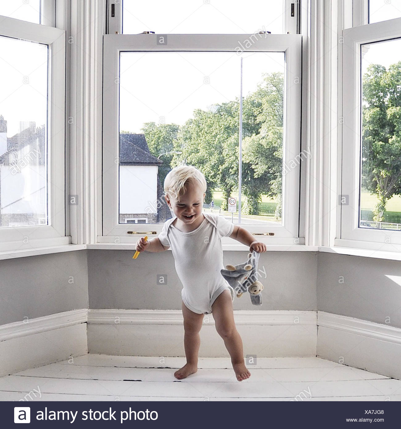 Boy dancing in living room holding toy - Stock Image