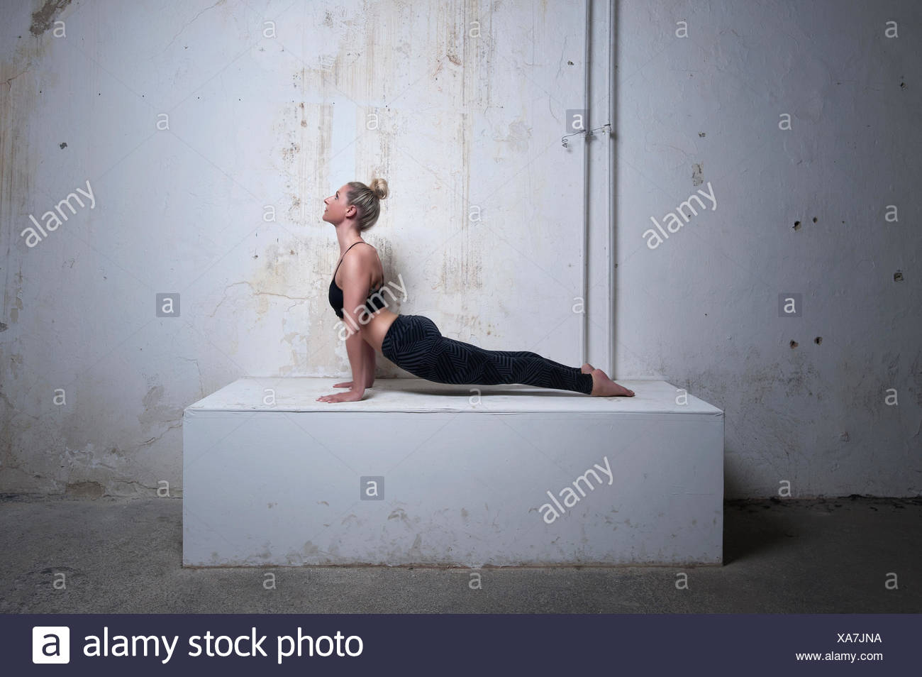 Mid adult woman practicing upward facing dog position on concrete block, Munich, Bavaria, Germany - Stock Image