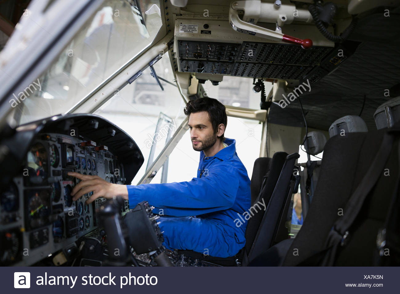 Helicopter mechanics working in cockpit - Stock Image