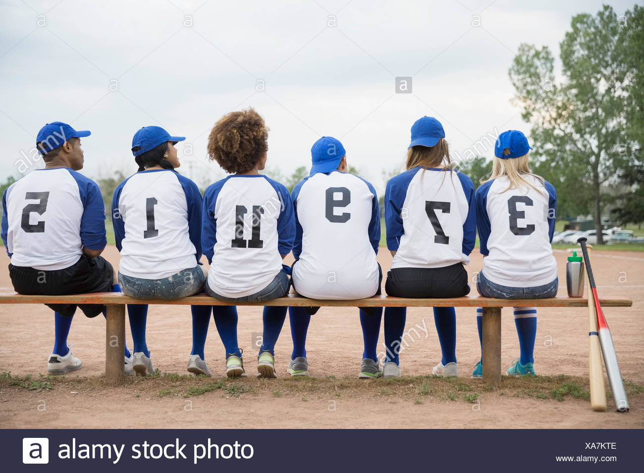 Baseball team sitting on bench in field - Stock Image
