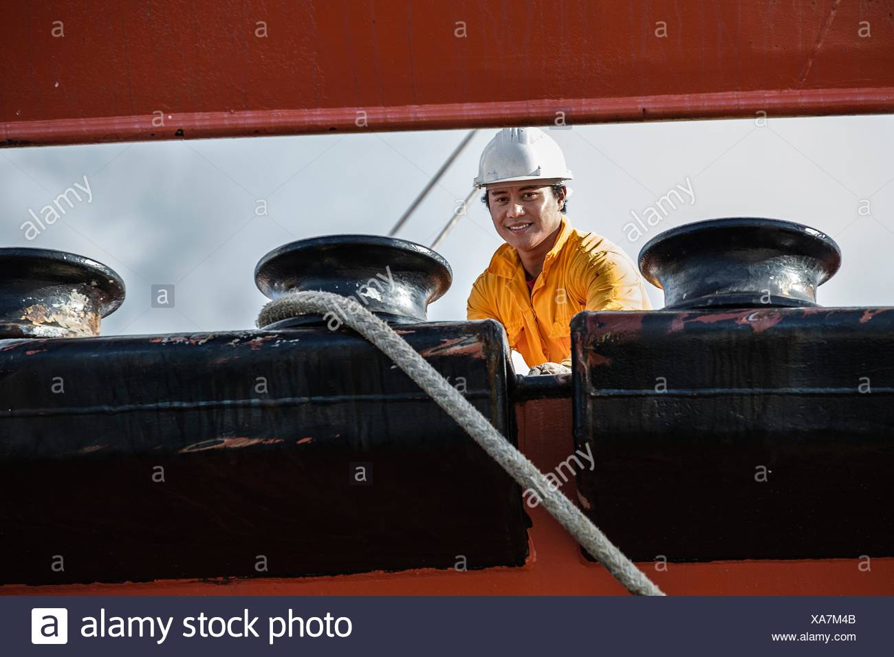 Worker fastening ropes to mooring posts on oil tanker - Stock Image