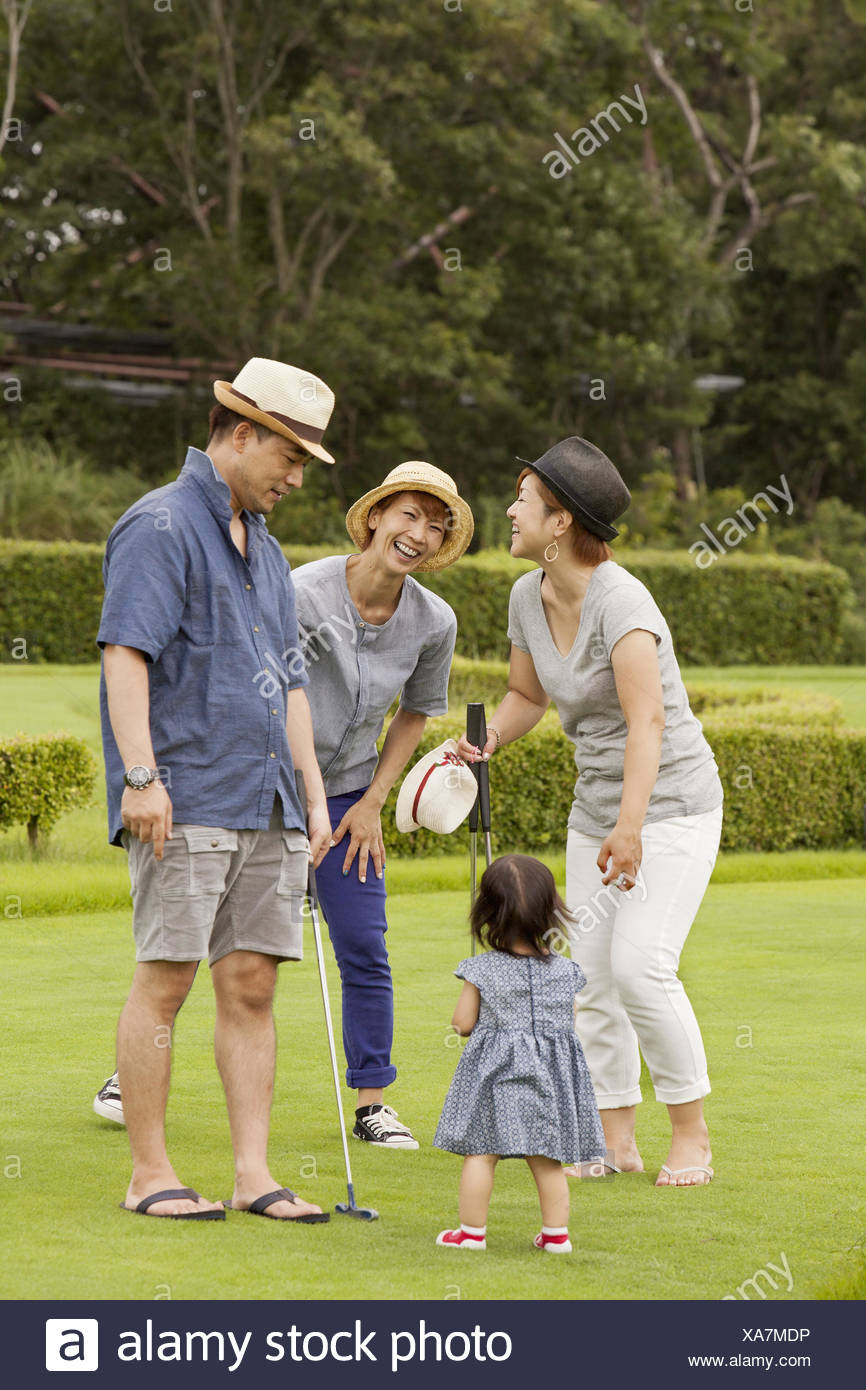 Family on a golf course.A child and three adults. - Stock Image