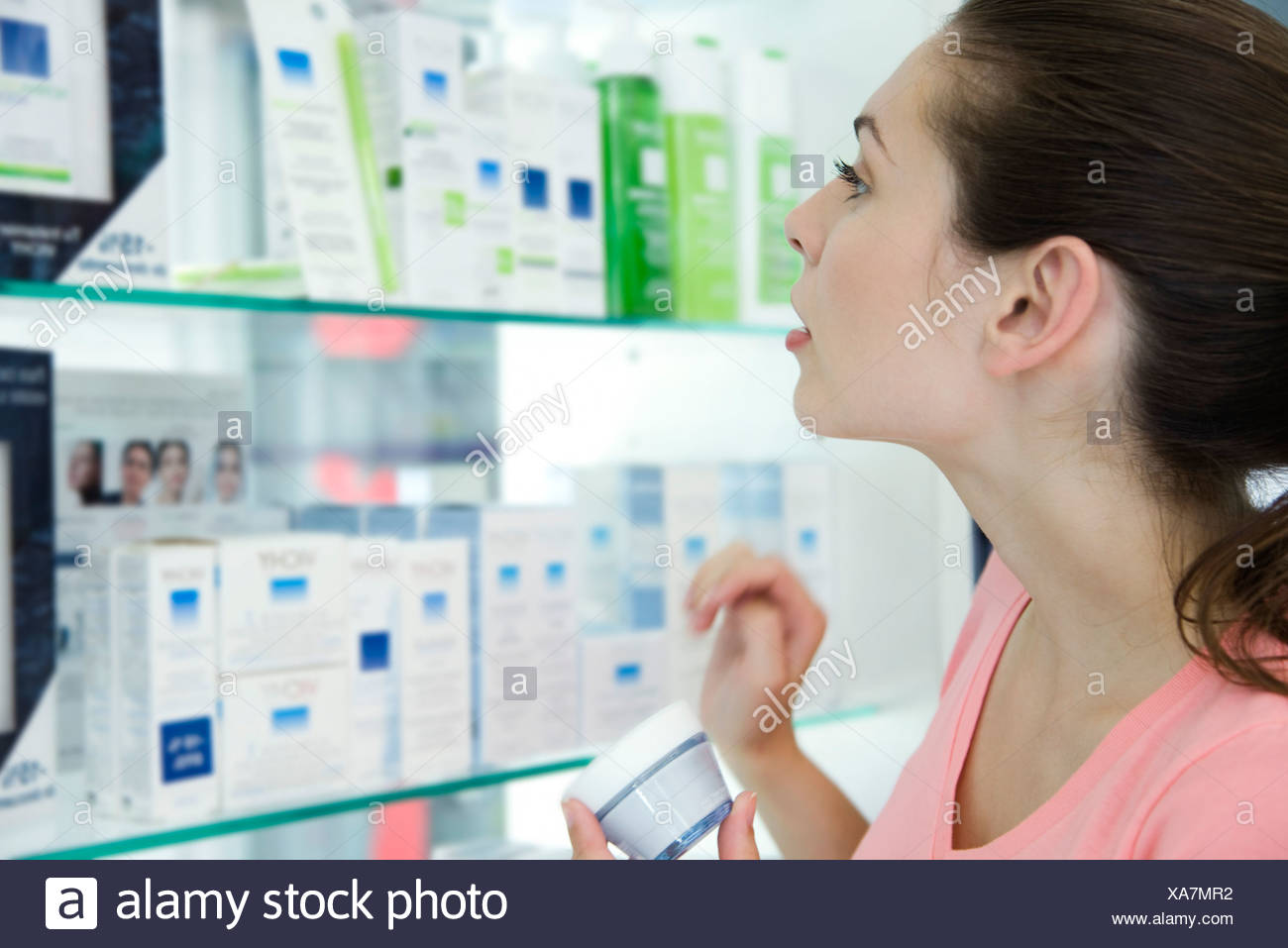 Young woman browsing beauty products in store - Stock Image