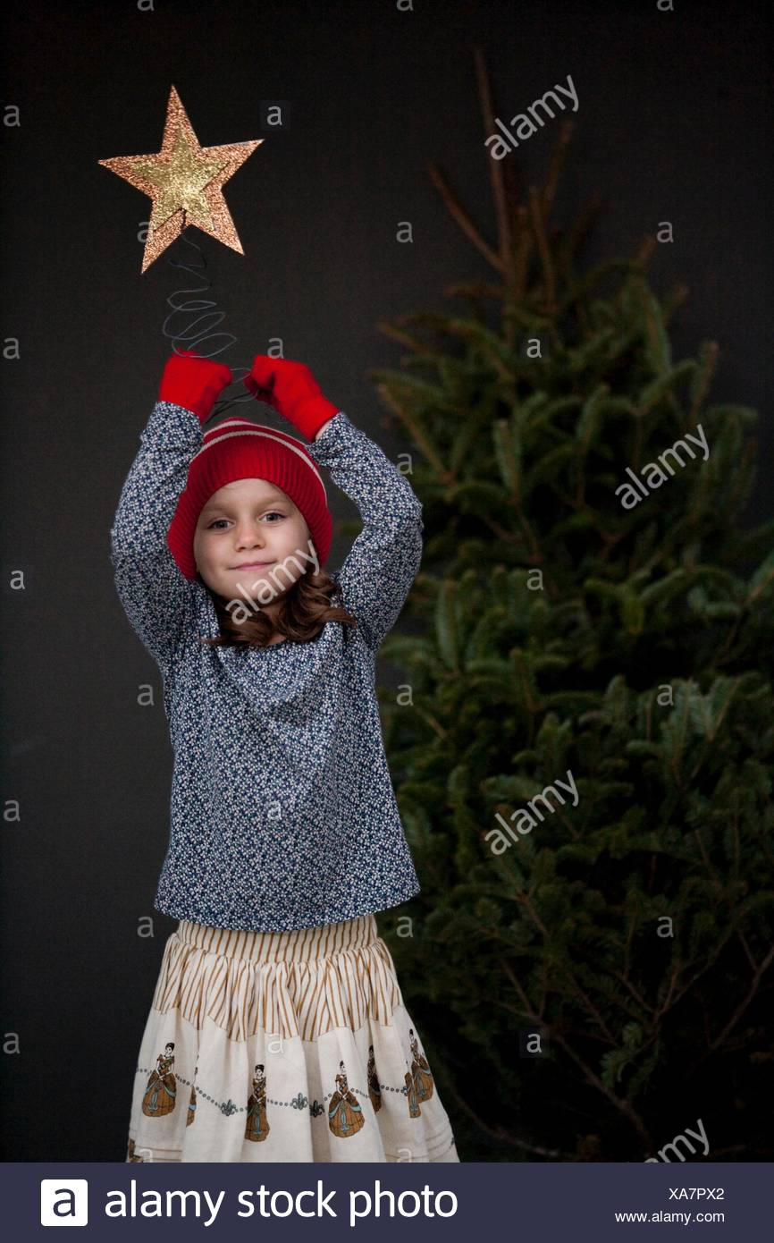 Portrait of a girl holding a christmas decoration - Stock Image