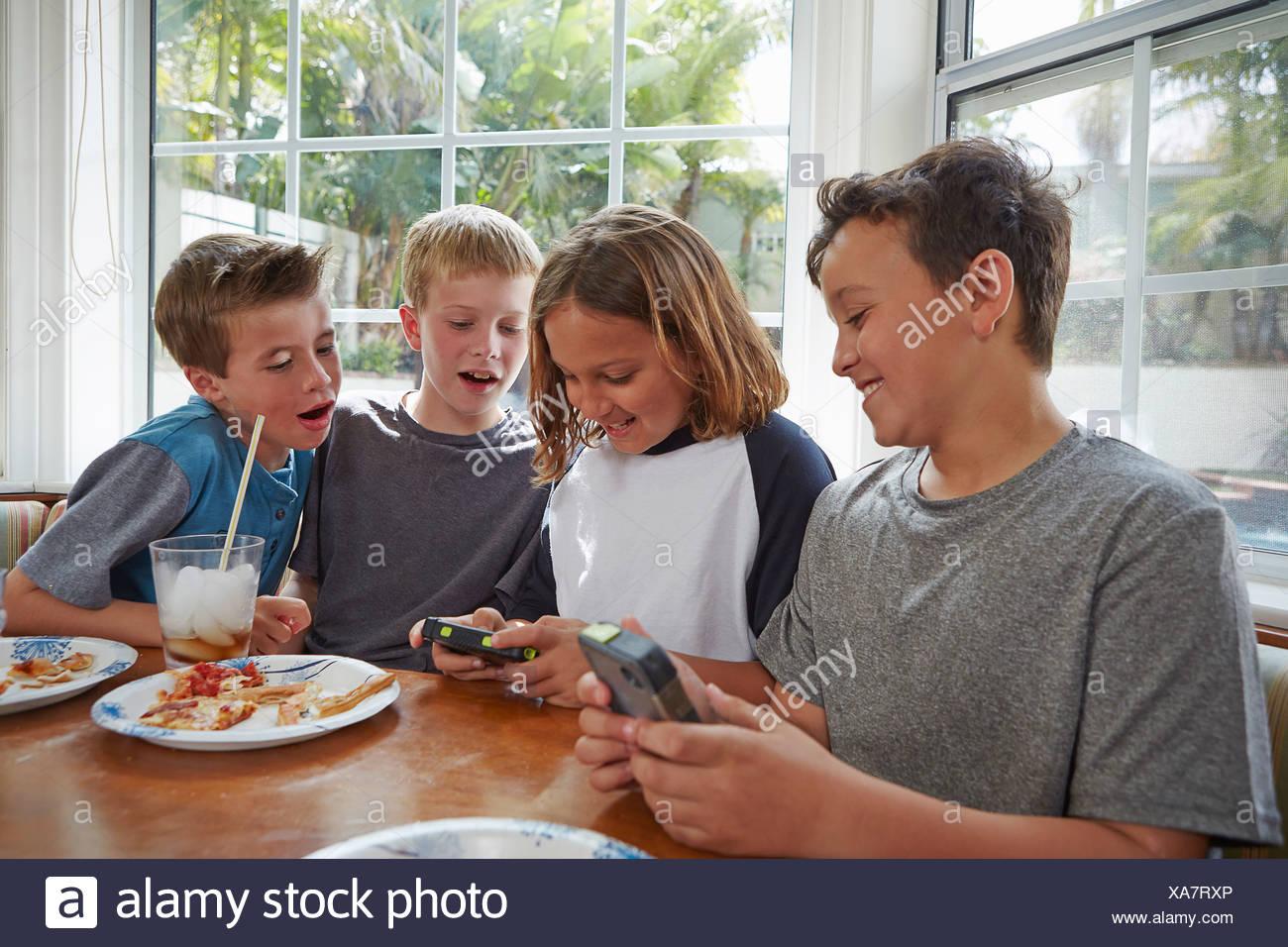 Boys playing handheld video games Stock Photo