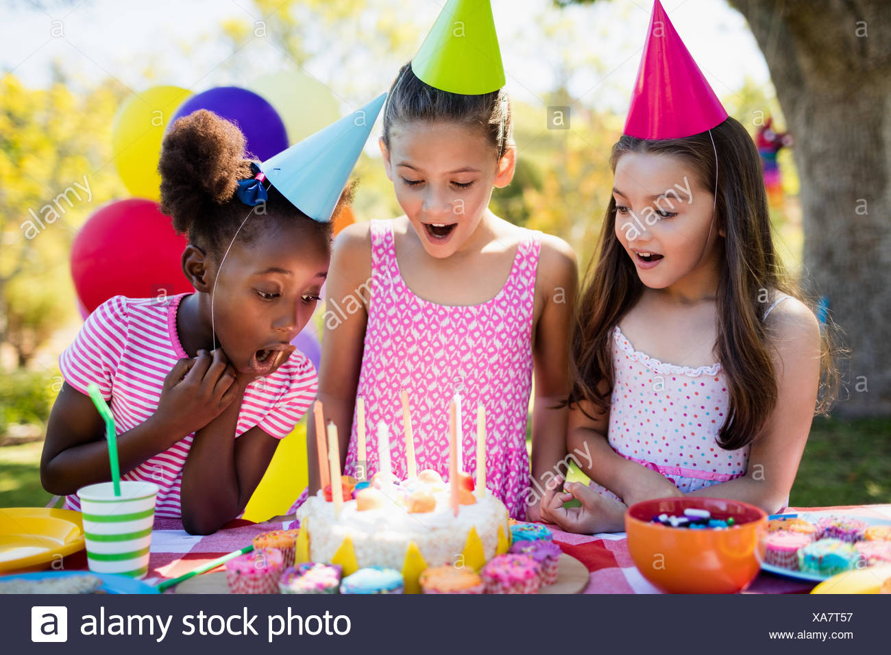 Portrait of cute girls preparing to blow on candle during a birthday party - Stock Image