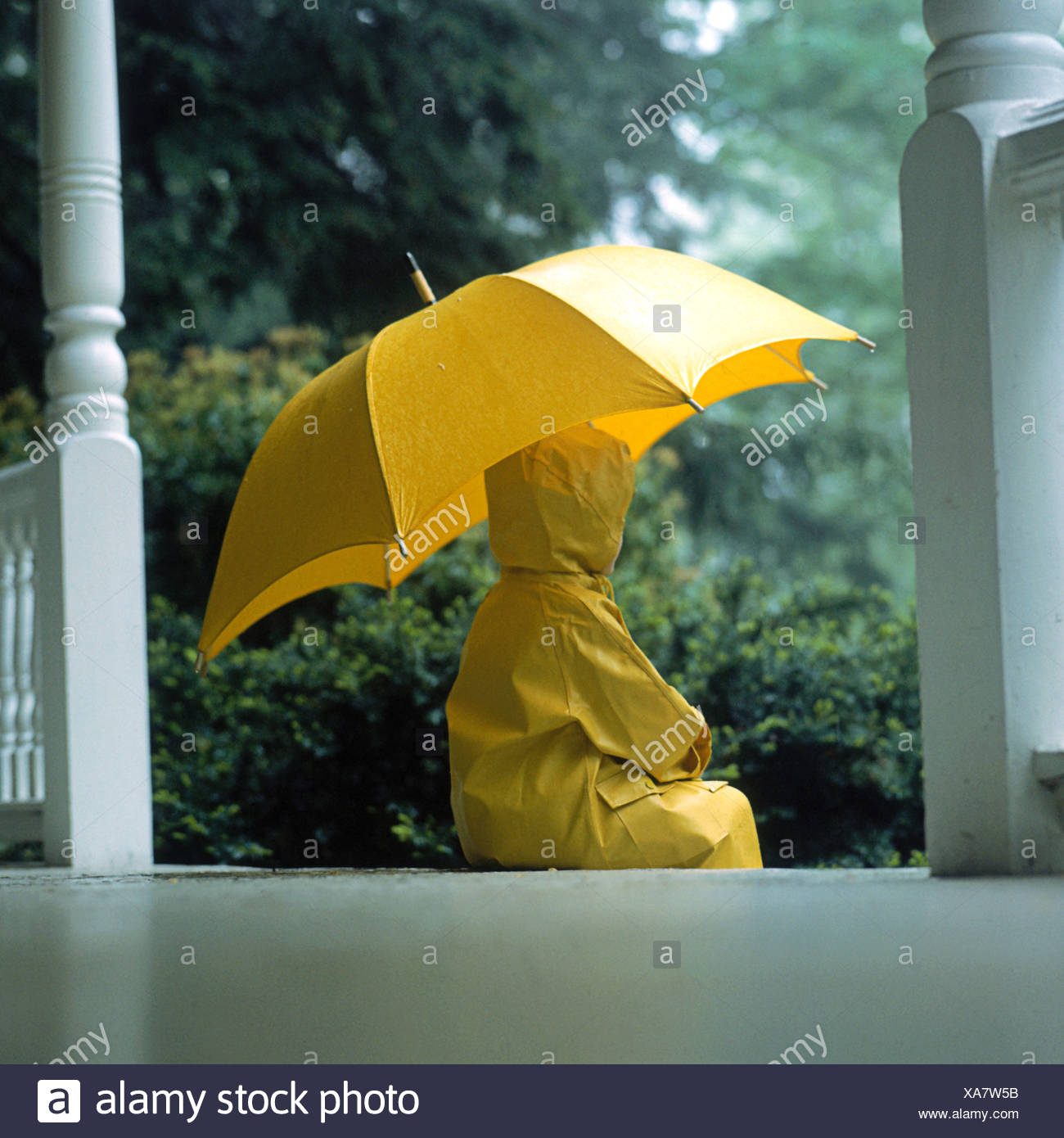 A young child wearing a yellow rain coat and rain boots standing in the rain holding a yellow umbrella - Stock Image