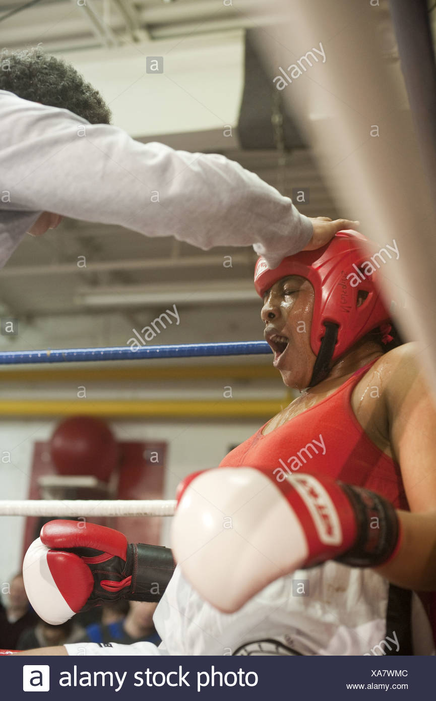 A female boxer catches her breadth while being coached between rounds at a fight, Toronto, Ontario - Stock Image