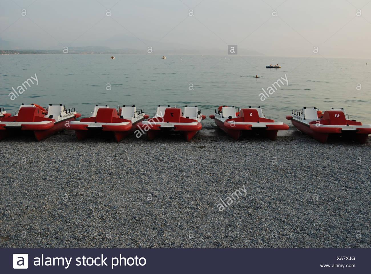 Fünf rot-weiße Tretboote liegen in einer Reihe am Kieselstrand bei Peschiera Stock Photo