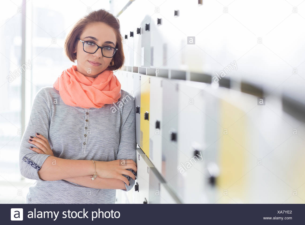 Portrait of confident businesswoman standing arms crossed in locker room at creative office - Stock Image