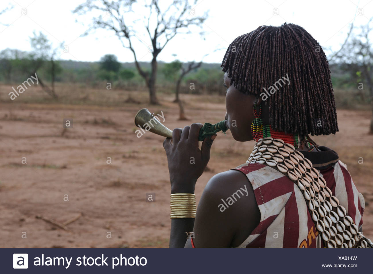 Young woman from the Hamar tribe blowing a horn in order to gain attention during the bull-leaping ceremony, an initiation rite - Stock Image