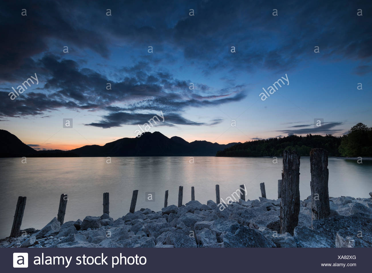 bank reinforcement of the Walchensee (Lake Walchen), in the background hazy contours of the Herzogstand (mountain) and Heimgarten in the Bavarian foothills. Longtime exposure shot shortly after sundown - Stock Image