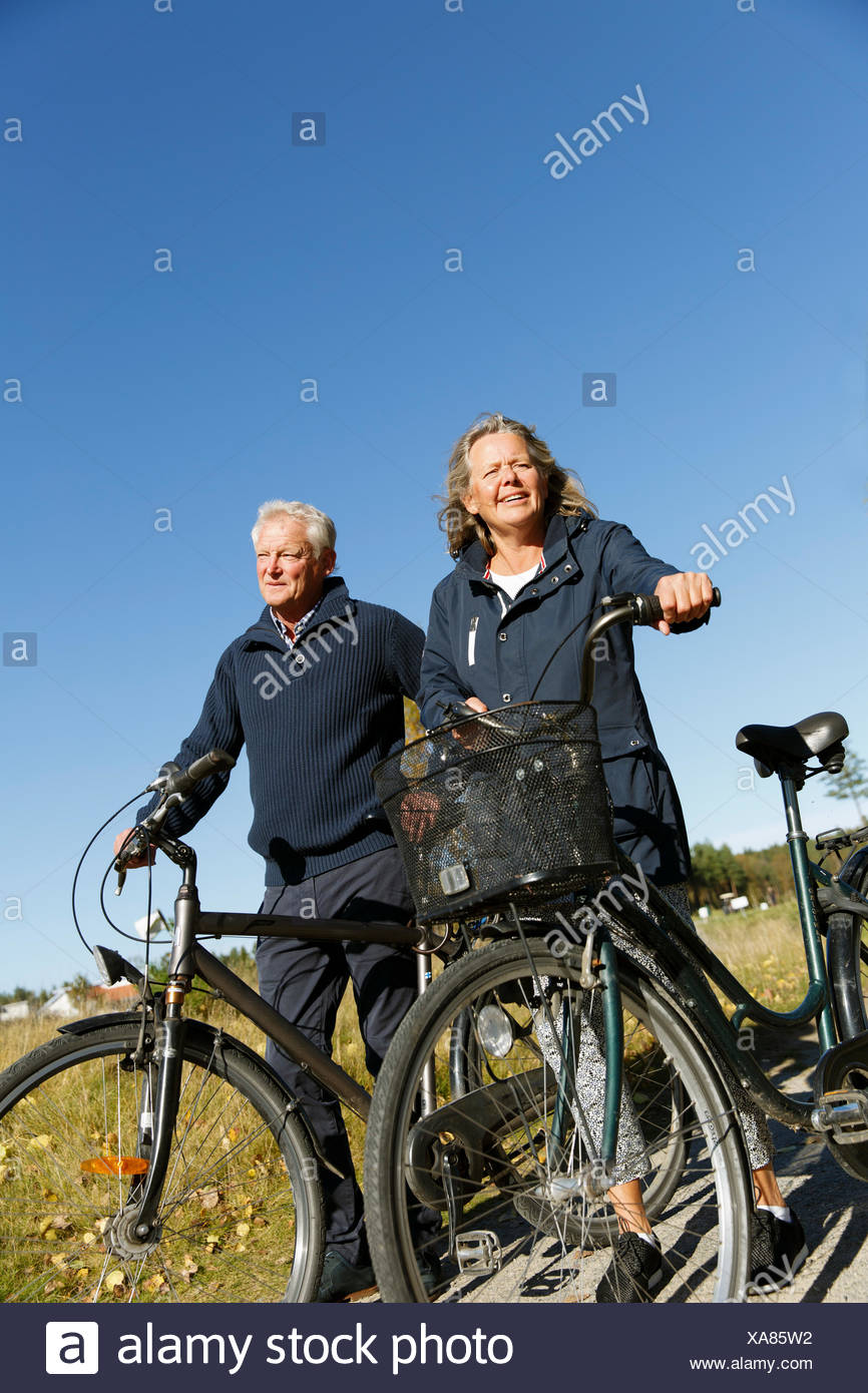 Sweden, Sodermanland, Senior man and mature woman walking with bicycles - Stock Image