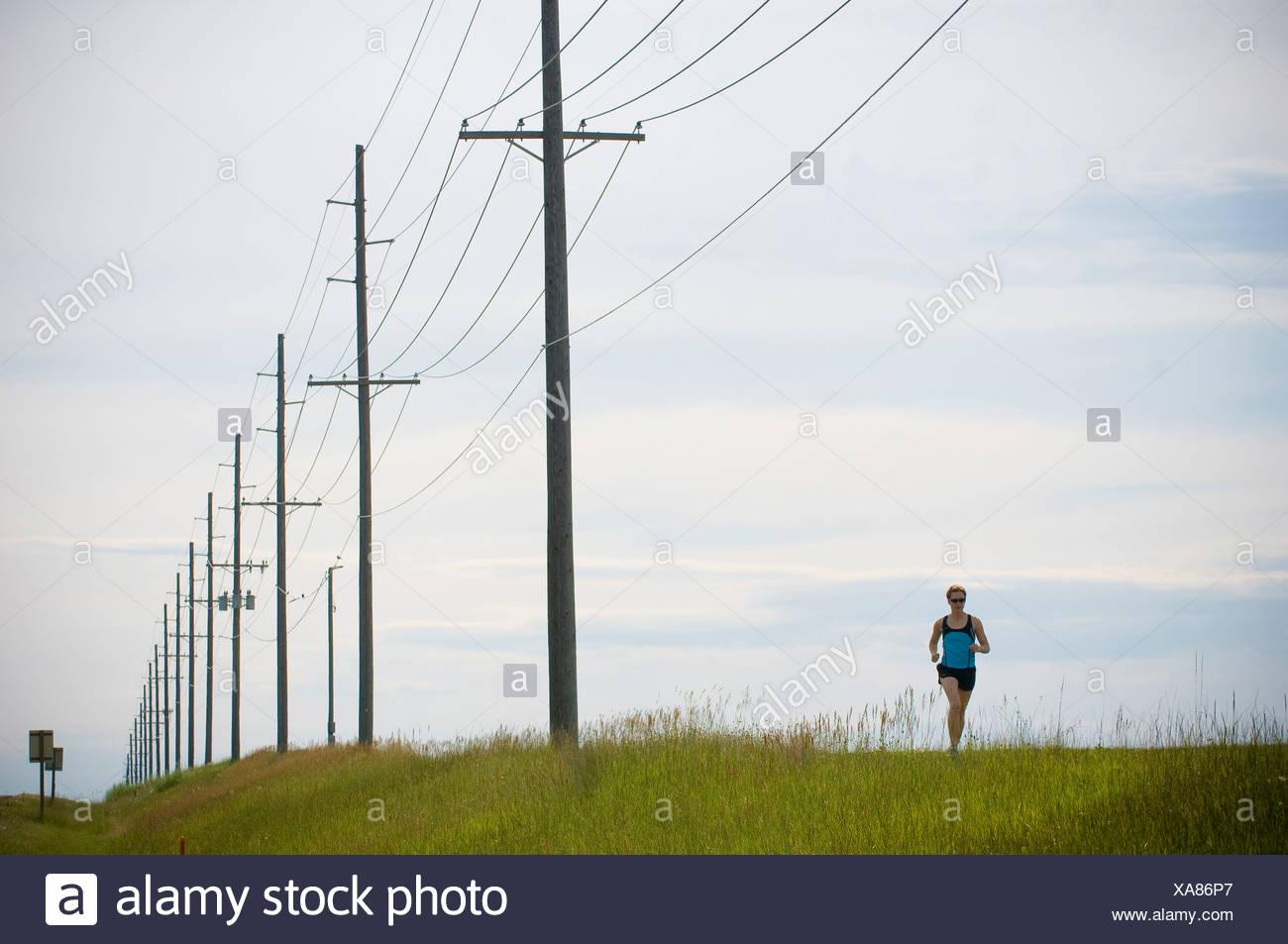 Woman running beneath power lines, Bozeman, Gallatin County, Montana, USA - Stock Image