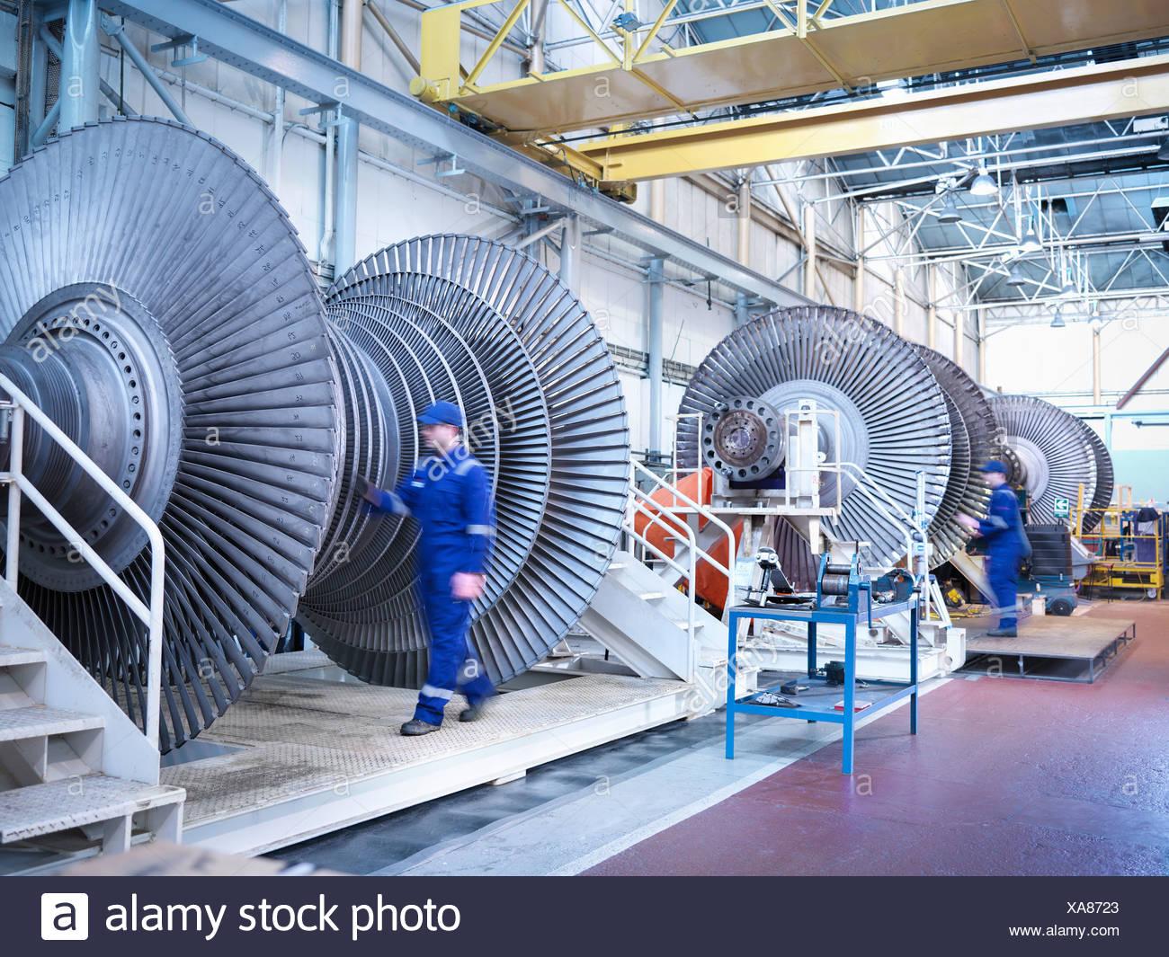 Engineers with low pressure steam turbines in repair bays in workshop Stock Photo