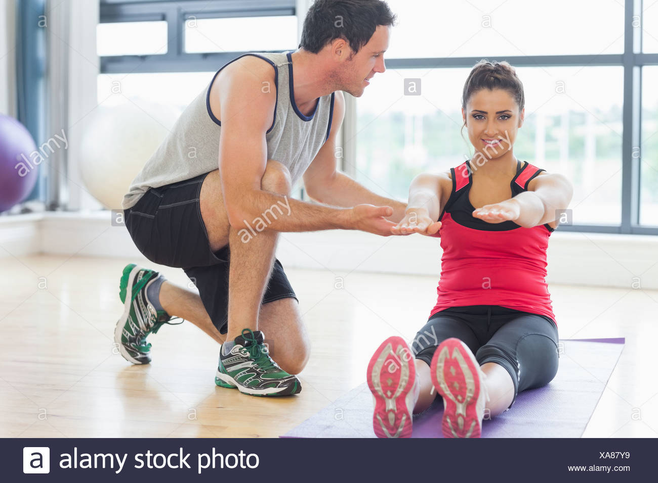 Male trainer assisting woman with pilate exercises in fitness studio - Stock Image