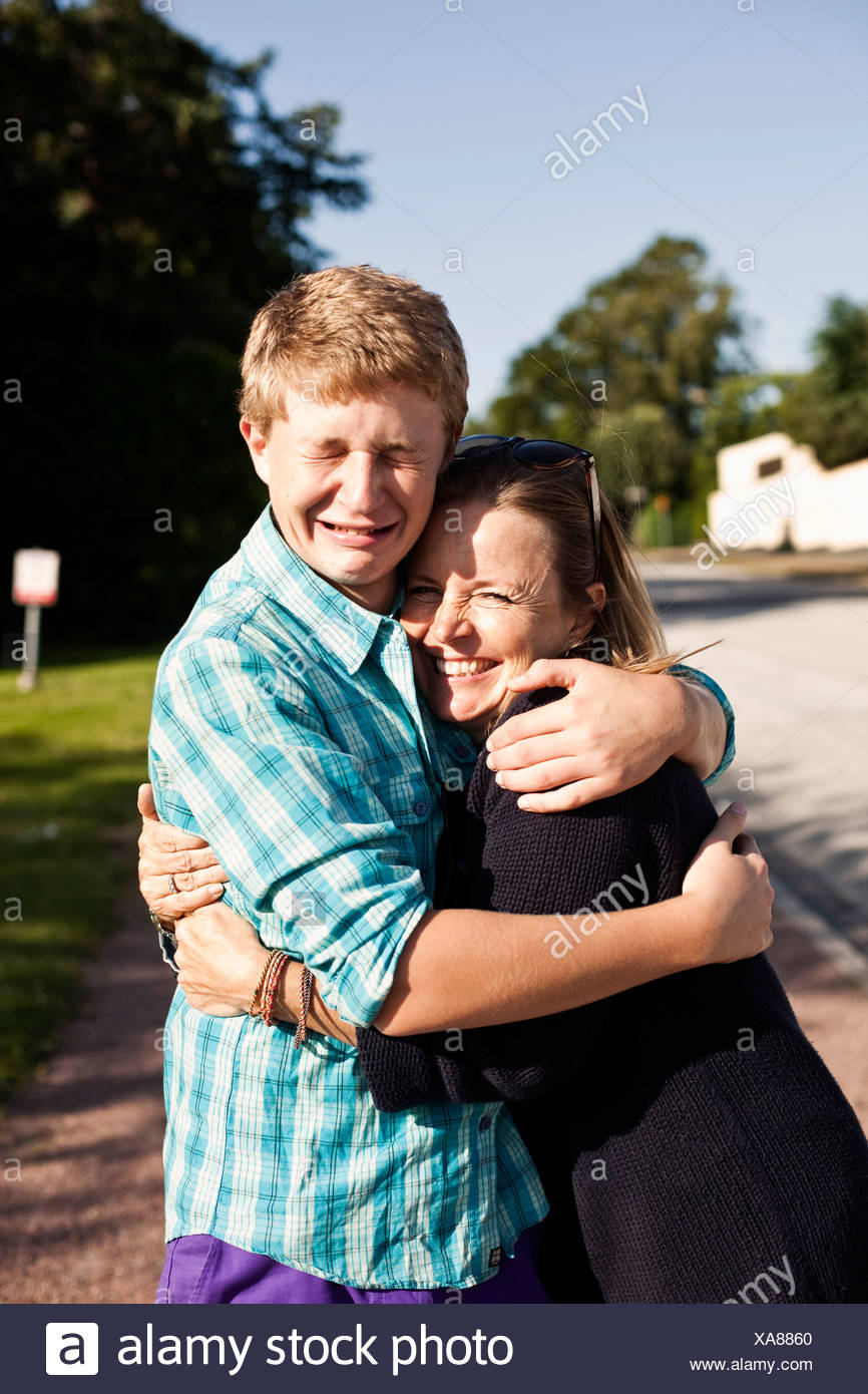 Portrait of happy woman embracing crying son - Stock Image