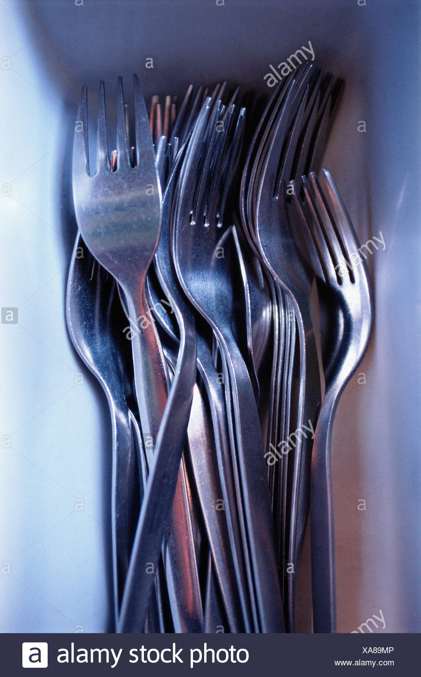 Stainless steel cutlery in tray - Stock Image