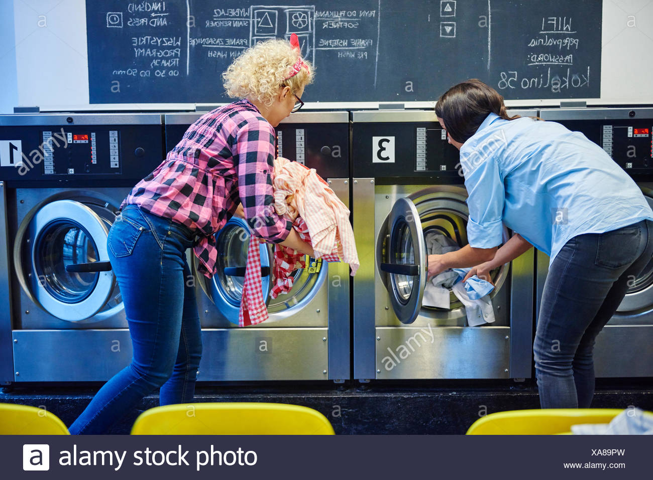 Two women inserting laundry into washing machines at laundrette - Stock Image