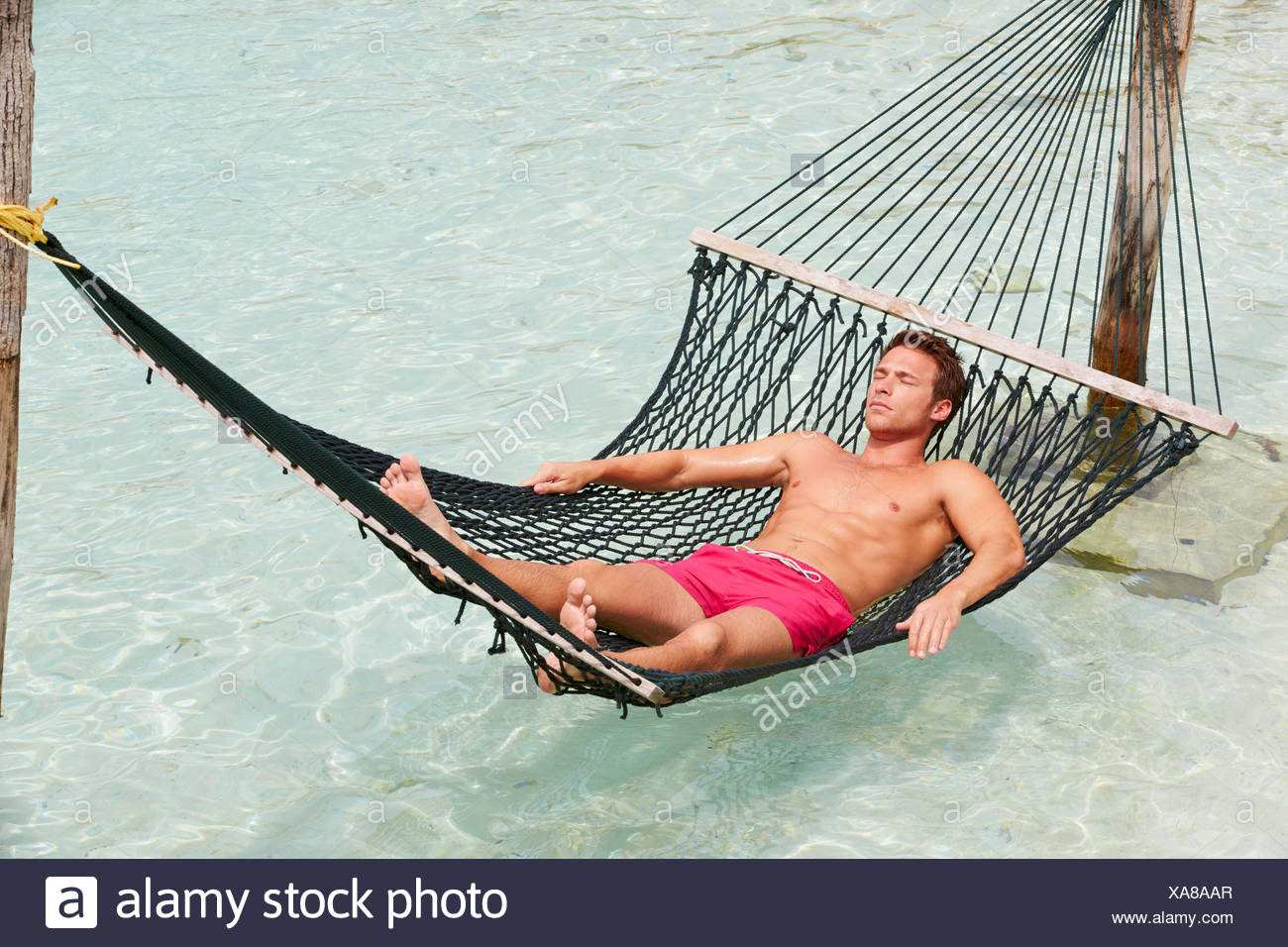 Man Relaxing In Beach Hammock - Stock Image