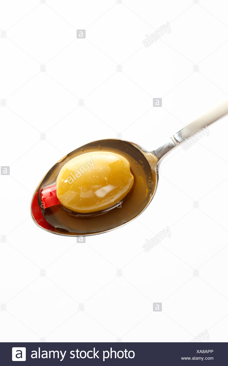 Preserved filled green olive on spoon against white background - Stock Image