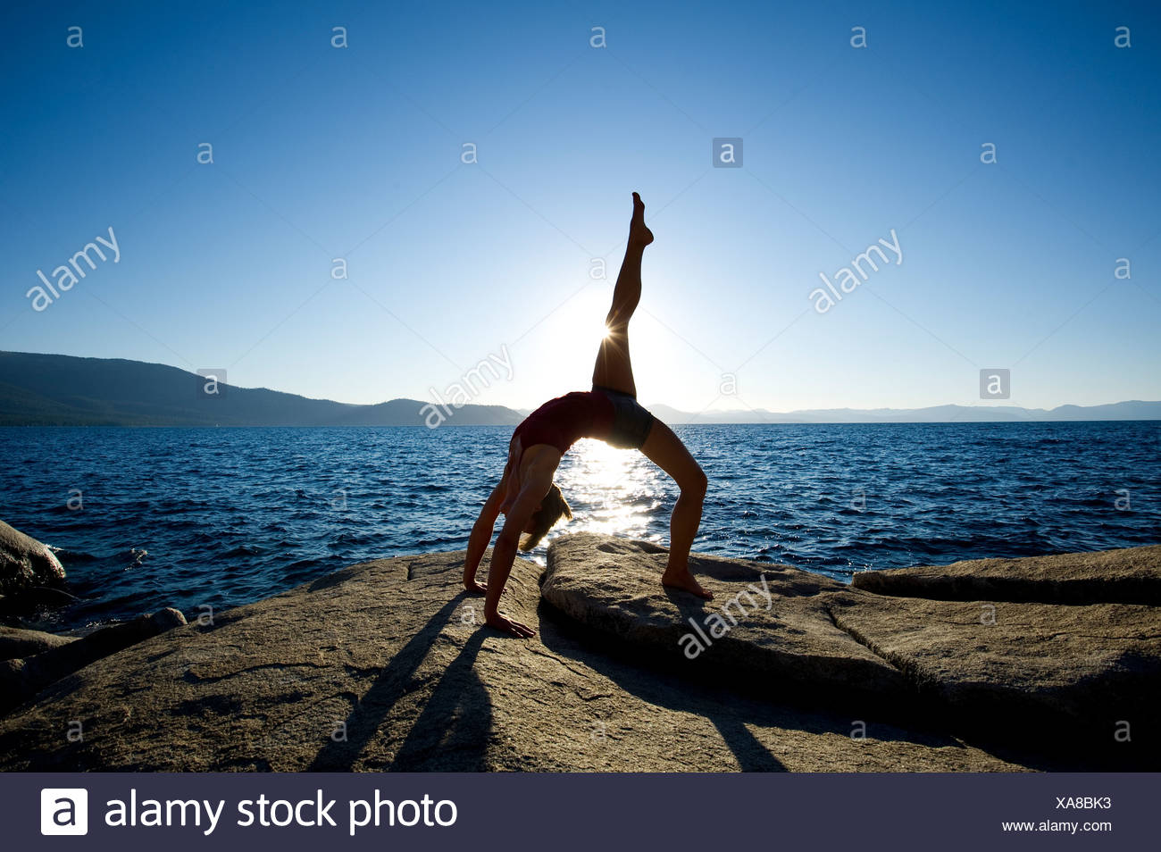 A silhouette of a young woman performing yoga on a granite boulder on the east shore of Lake Tahoe, NV. - Stock Image