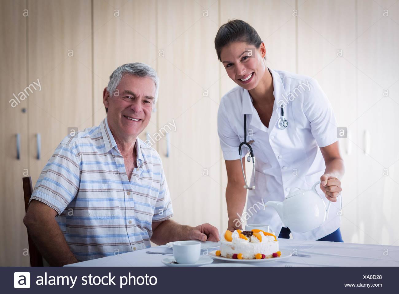 Portrait Of Female Doctor Celebration Seniors Man Birthday In Living Room