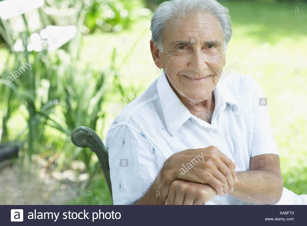 Senior man sitting outdoors smiling - Stock Image