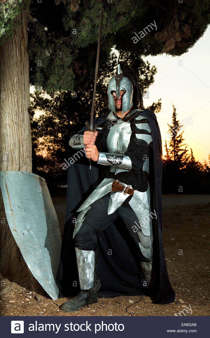 A knight in shining armour wielding sword at sunset. Model Release Available - Stock Image