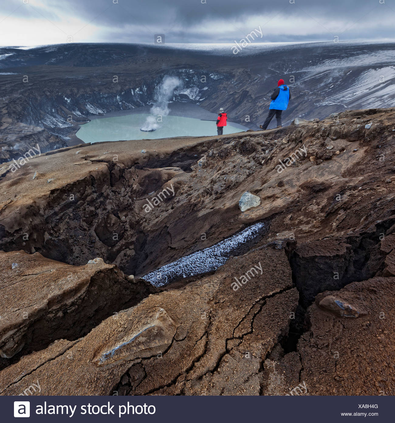 Scientist viewing steaming crater after Grimsvotn eruption, Iceland - Stock Image