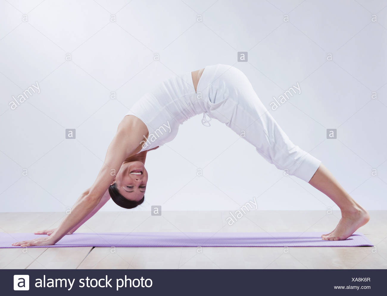 Mid adult woman doing downward facing dog position against white background, smiling, portrait - Stock Image