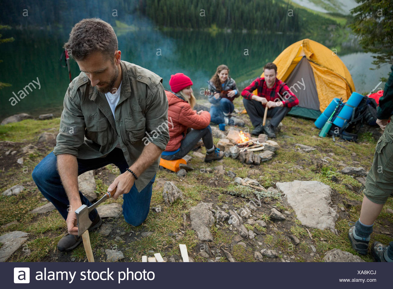 Man splitting wood with ax near campfire at lakeside campsite - Stock Image