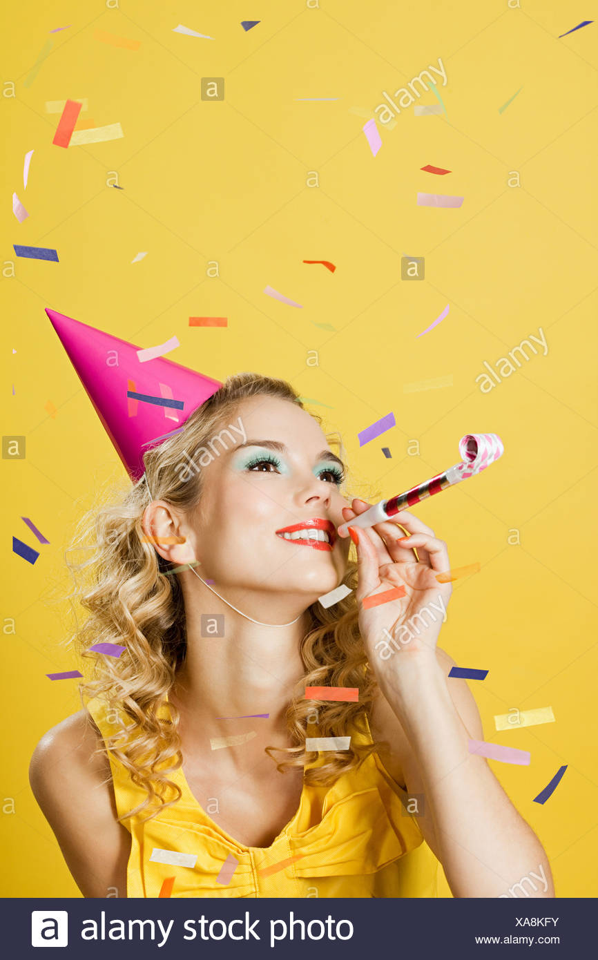 Young woman wearing party hat with party blower and confetti - Stock Image
