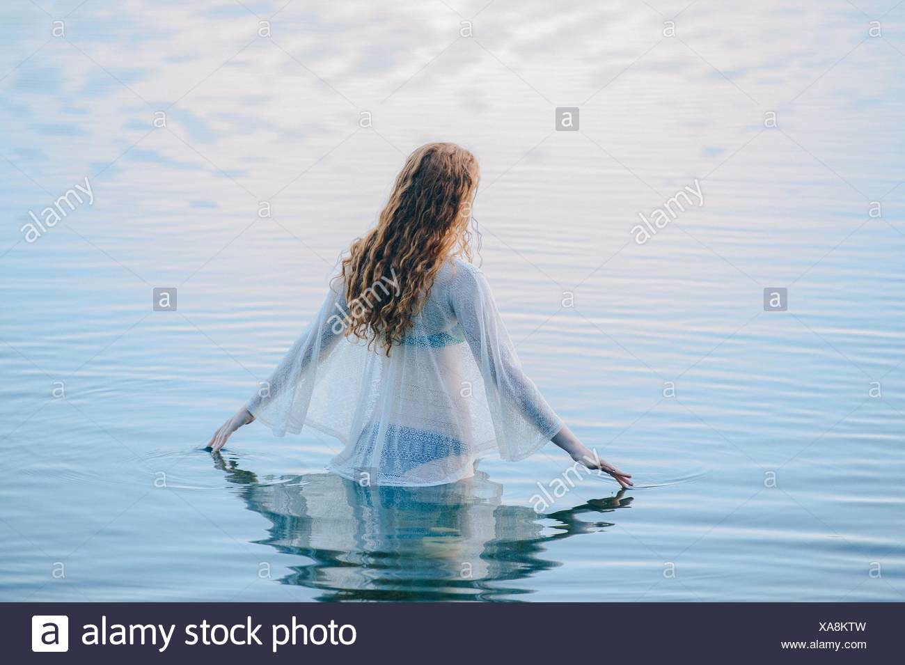 Rear view of young woman standing in lake rippling surface with her fingers - Stock Image