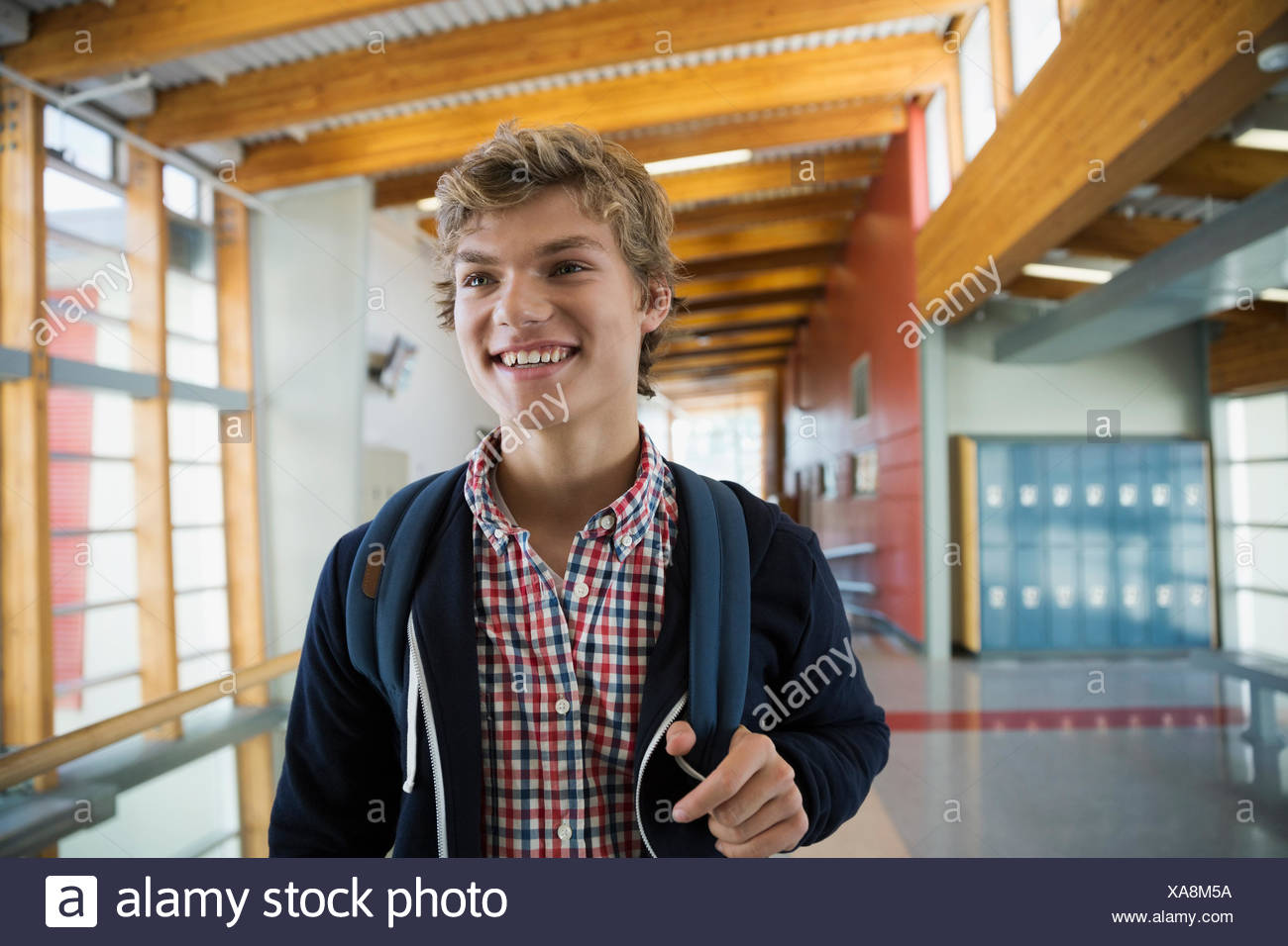 Smiling high school student in corridor - Stock Image