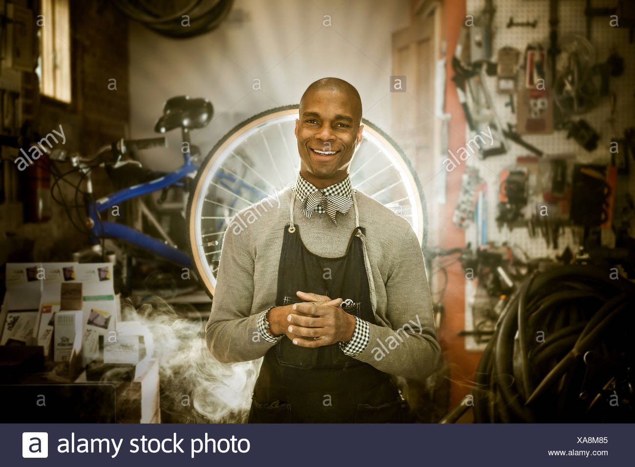 Bike mechanic against backdrop of heavenly rays of light - Stock Image
