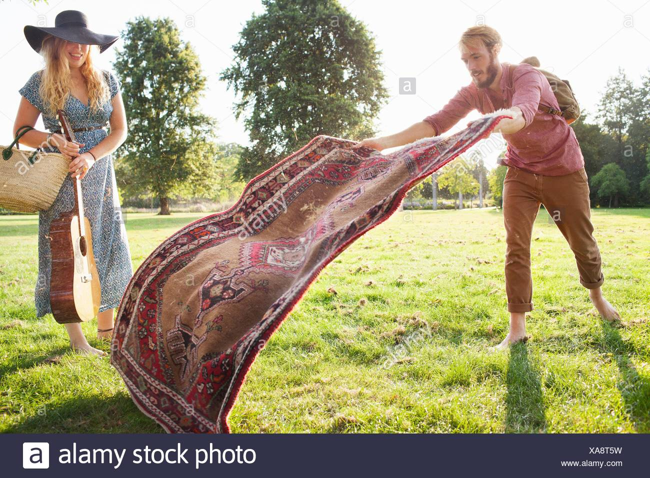 Romantic young couple spreading rug for picnic in park - Stock Image