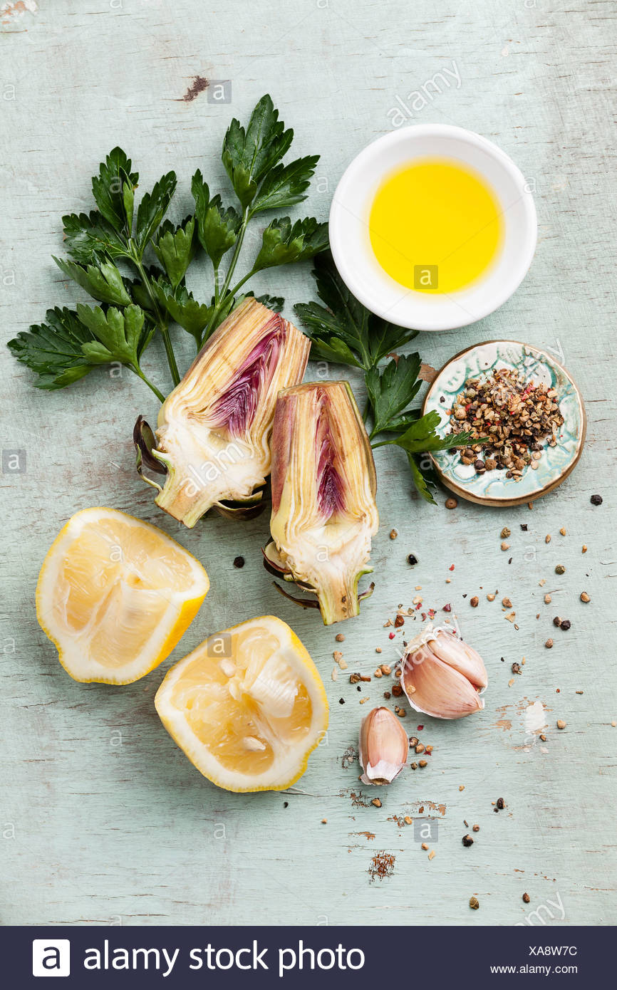 Ingredients for cooking artichokes - lemon, parsley, garlic, spices - Stock Image