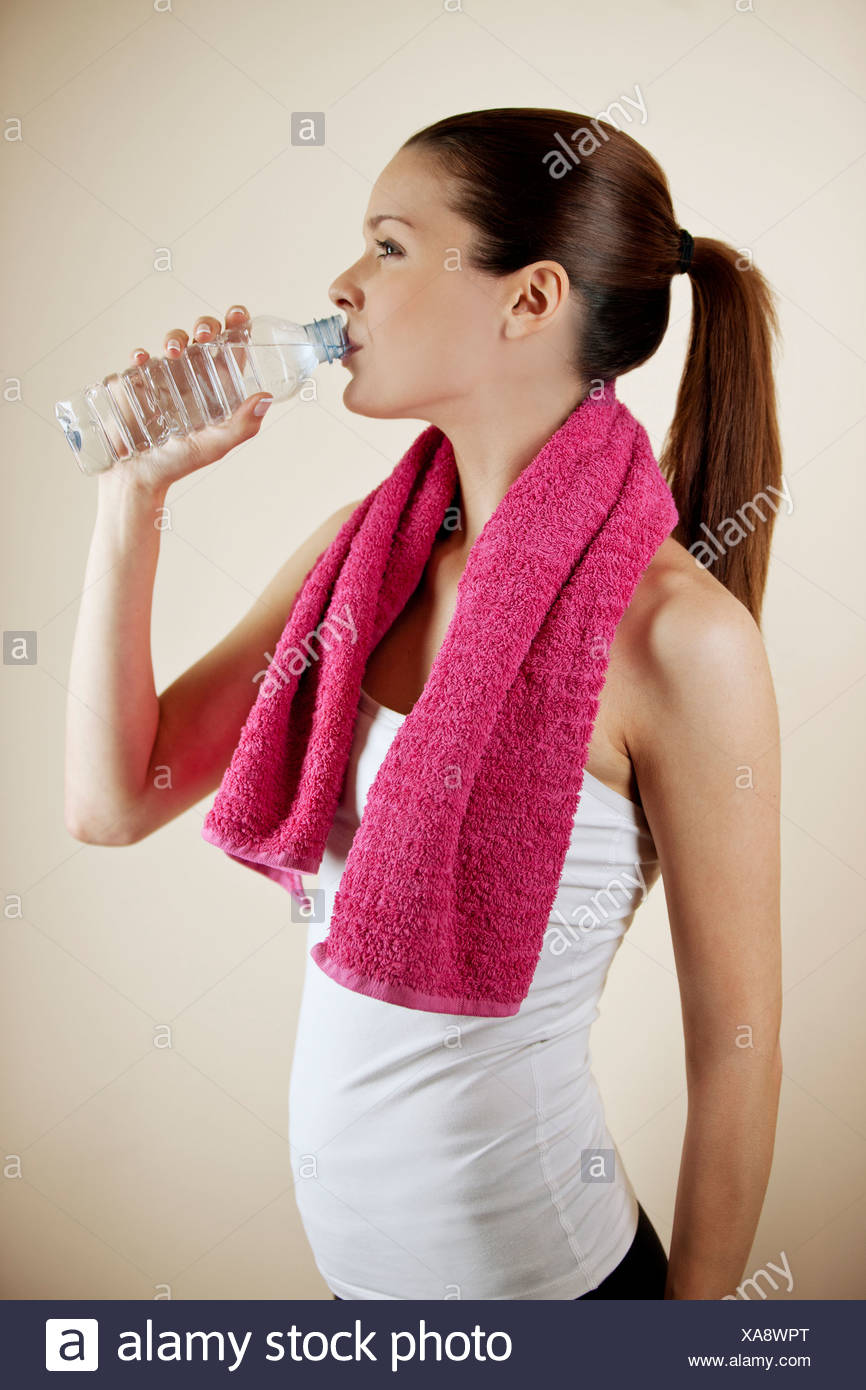 A young woman wearing fitness clothing, drinking a bottle of water - Stock Image