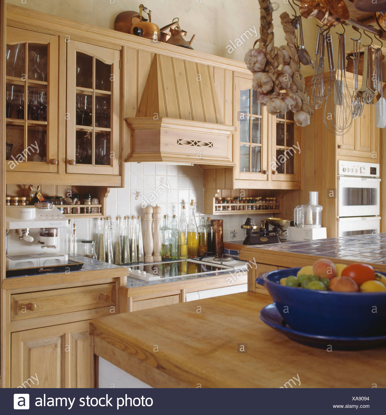Bowl Of Fruit On Wooden Worktop In Fitted Wooden Kitchen With Row Of