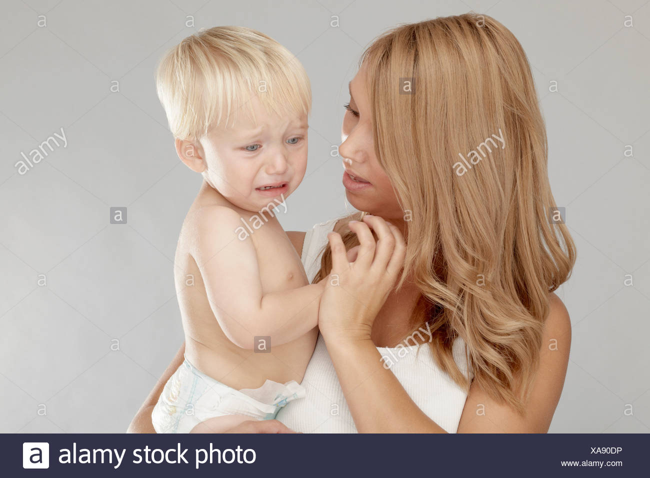 Mother holding crying baby boy - Stock Image