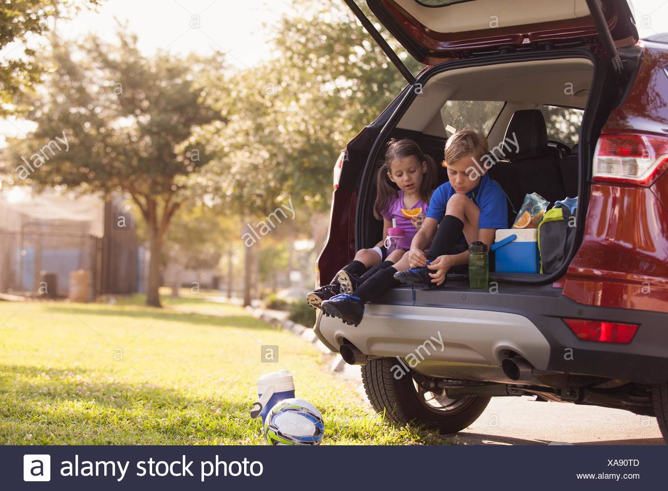 Boy and younger sister preparing for football practice whist sitting in car boot - Stock Image
