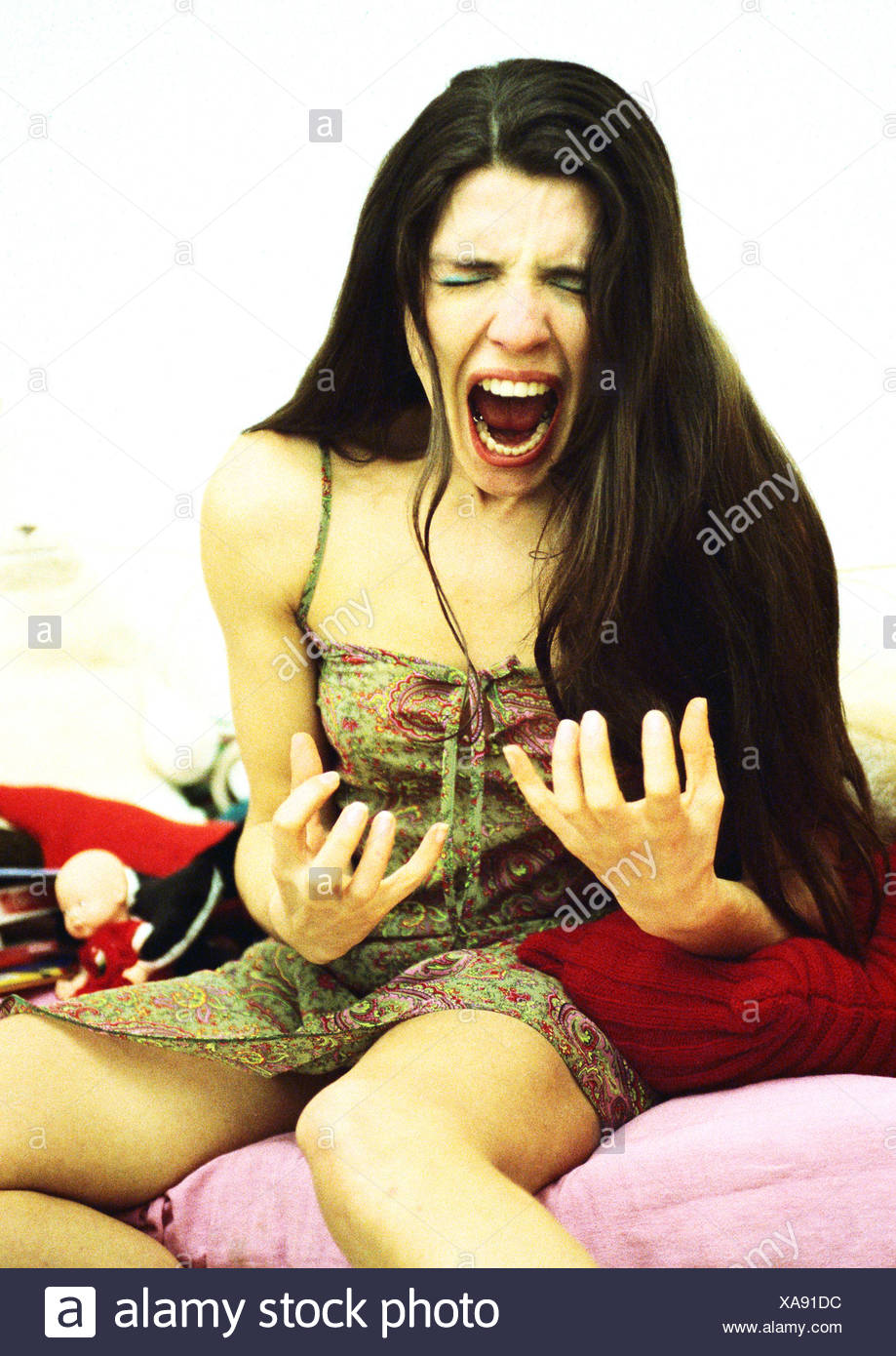 Woman sitting on bed screaming, portrait. - Stock Image