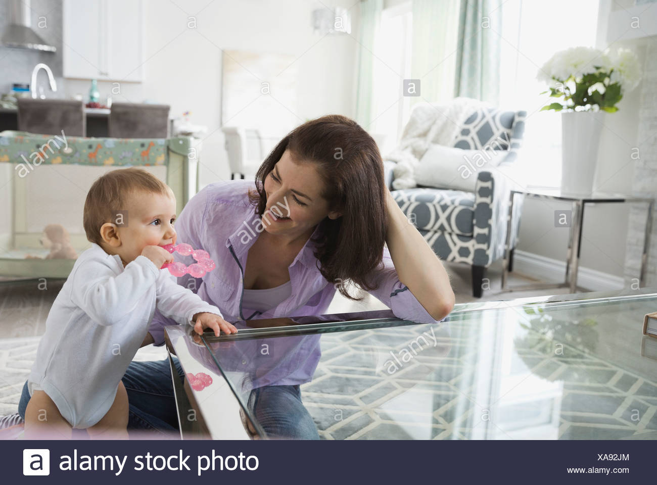 Mother with cute baby girl at home - Stock Image